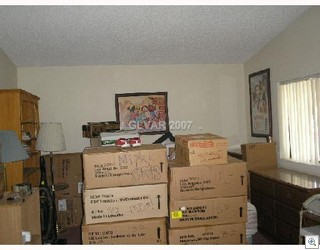All that wasted floor space in front of the bed...We could put some of the boxes there!