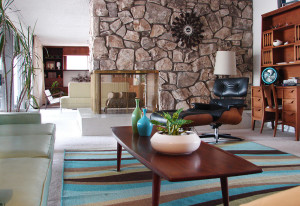 The stacked stone peninsula fireplace separates the living room from the family room. The hearth is original terrazzo from 1963.